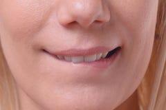 Durchdachte blonde Frau, die ihre Lippe beißt Stockfoto