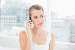 Durchdachte blonde Frau am Telefon Stockbilder