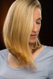Durchdachte blonde junge Frau, die unten schaut Lizenzfreie Stockfotos