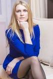 Durchdachte blonde kaukasische Frau im blauen Kleid, das auf Couch sitzt Stockfotos