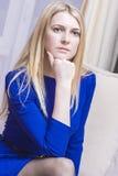 Durchdachte blonde kaukasische Frau im blauen Kleid, das auf Couch sitzt Lizenzfreies Stockbild