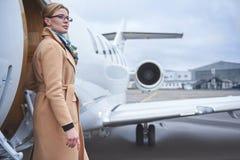Durchdachte Dame, die nahe Flugzeugen aufstellt stockfoto
