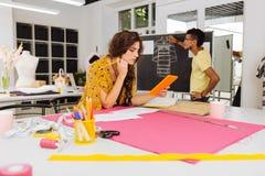 Durchdachte Damenschneiderin, welche die Tabelle beim Arbeiten mit Kollegen betrachtet lizenzfreie stockfotografie