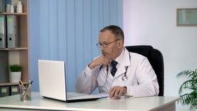 Durchdachte Doktorleseinformationen über den Laptop, denkend auf geduldiger Diagnose lizenzfreie stockfotos