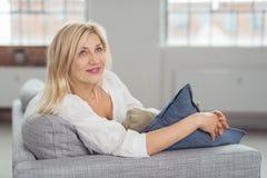 Durchdachte erwachsene Dame auf Gray Couch Looking Up Lizenzfreies Stockfoto