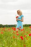 Durchdachte Frau auf dem Mohnblumegebiet Stockfotos