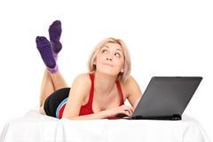 Durchdachte Frau auf einem Bett, das an einem Laptop arbeitet Lizenzfreies Stockfoto