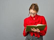 Durchdachte Frau in der roten Bluse, die auf ihren Anmerkungen schaut Lizenzfreies Stockfoto