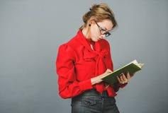 Durchdachte Frau in der roten Bluse, die auf ihren Anmerkungen schaut Lizenzfreie Stockbilder