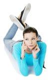 Durchdachte Frau in der zufälligen Kleidung, die auf Boden liegt Stockbilder