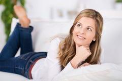 Durchdachte Frau, die auf Couch liegt Stockfotografie
