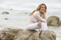 Durchdachte Frau, die auf Felsen am Strand sitzt Lizenzfreie Stockbilder