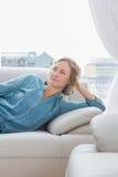 Durchdachte Frau, die auf ihrer Couch sich entspannt Stockbild