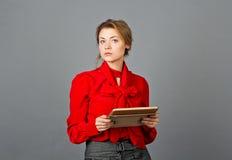 Durchdachte Frau, die beim Denken weg schaut Ablesen ihrer Tablette Stockfoto