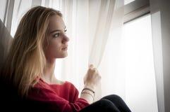 Durchdachte Frau, die heraus Fenster schaut Lizenzfreie Stockfotografie