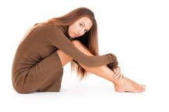 Durchdachte Frau, die ihre Fahrwerkbeine umfaßt lizenzfreies stockbild