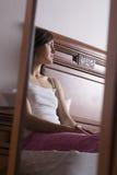 Durchdachte Frau, die im Spiegel am Schlafzimmer sich reflektiert Lizenzfreie Stockfotografie