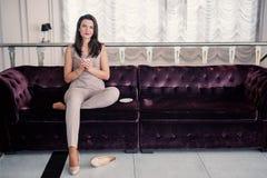 Durchdachte Frau, die Kaffeetasse ond zu Hause l?chelt beim Sitzen auf der Couch h?lt Kopieren Sie Platz lizenzfreie stockfotografie