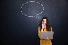 Durchdachte Frau, die Laptop über Tafelhintergrund mit Spracheblase verwendet Stockbilder