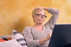 Durchdachte Frau, die am Sofa mit Laptop sitzt Stockbild