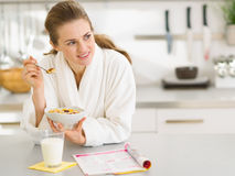 Durchdachte Frau im Bademantel Frühstück essend Lizenzfreies Stockbild