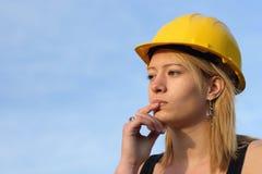 Durchdachte Frau im harten Hut. Lizenzfreies Stockfoto