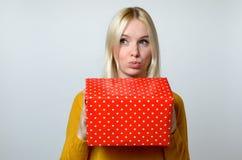 Durchdachte Frau mit den schmollenden Lippen, die Geschenk halten Lizenzfreie Stockfotografie