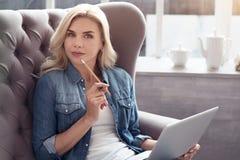 Durchdachte Frau mit Laptop zu Hause Lizenzfreies Stockbild