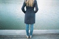 Durchdachte Frau, undeutlichen See beobachtend Stockbild