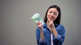 Durchdachte Frau, welche die Eurobanknoten, denkend an die Investierung des Geldes, Ablagerung h?lt stockfoto
