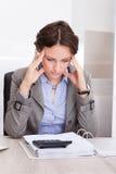 Durchdachte Geschäftsfrau, die Berechnungen tut Stockfotos