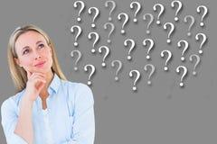 Durchdachte Geschäftsfrau, die Fragezeichen gegen grauen Hintergrund betrachtet Lizenzfreie Stockfotografie