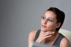 Durchdachte Geschäftsfrau, die im Büro denkt Stockfotografie