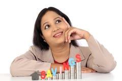 Durchdachte Geschäftsfrau mit Stapel Münzen lizenzfreie stockfotografie