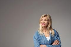 Durchdachte glückliche Frau auf Grau mit Kopien-Raum Stockfotos