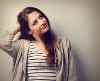 Durchdachte glückliche schöne junge Frau, die den Kopf und den Blick hält Lizenzfreies Stockbild