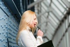 Durchdachte Ingwerfrau mit rotem Lippenbehälter und -notizbuch stockfoto