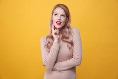 Durchdachte junge blonde Dame mit den hellen Make-uplippen Stockbilder