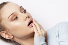 Durchdachte junge blonde Frau gegen weißen Hintergrund Lizenzfreies Stockfoto