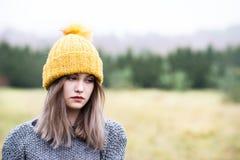 Durchdachte junge Frau in der woolen gelben Kappe lizenzfreies stockfoto