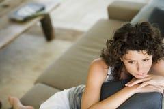 Durchdachte junge Frau, die auf Couch sitzt Stockfotos