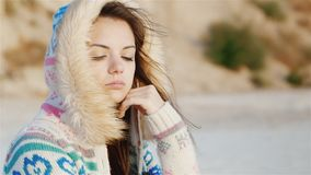Durchdachte junge Frau, die auf dem Strand, der Wind durchbrennt in ihrem Gesicht sitzt K?hler Tag Zeit zu tr?umen stock video