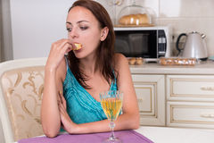 Durchdachte junge Frau, die in der Küche isst Lizenzfreies Stockfoto