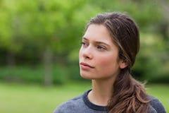 Durchdachte junge Frau, die in einem Park steht Stockfoto