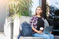 Durchdachte junge Frau, die Laptop im Café verwendet Stockbild