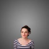 Durchdachte junge Frau, die mit Kopienraum gestikuliert Lizenzfreies Stockfoto