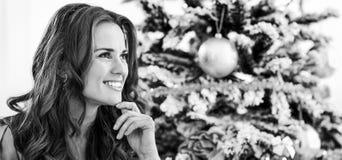 Durchdachte junge Frau, die nahe Weihnachtsbaum sitzt lizenzfreie stockfotos