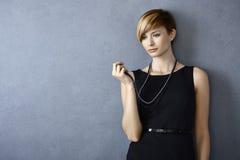 Durchdachte junge Frau, die Perlenhalskette betrachtet Lizenzfreies Stockfoto