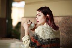 Durchdachte junge Frau im Sommercafé mit Tasse Kaffee lizenzfreies stockfoto