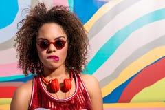 Durchdachte junge Frau mit Kopfhörer auf Hals Lizenzfreies Stockfoto